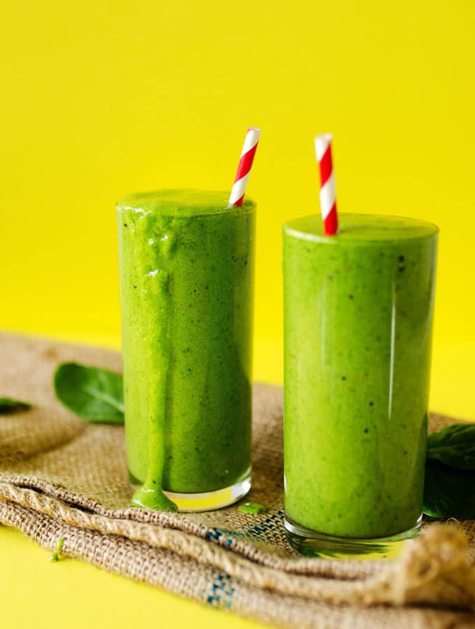 Green smoothie picture in a glass with a striped straw and a yellow background
