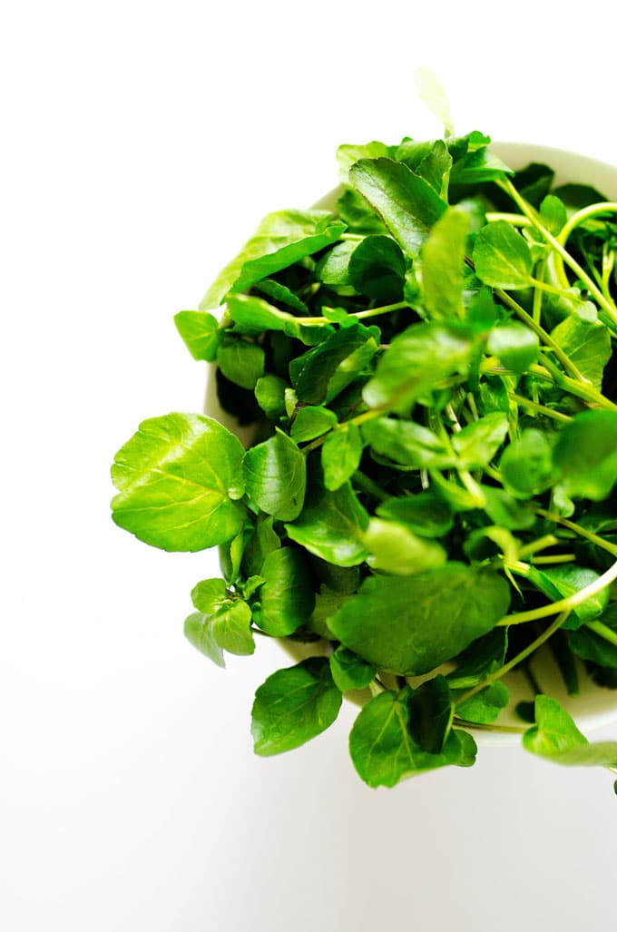 Watercress leaves in a bowl on a white background