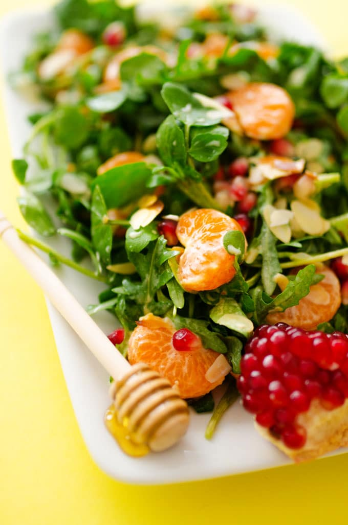 Watercress salad with orange and pomegranate on a yellow background