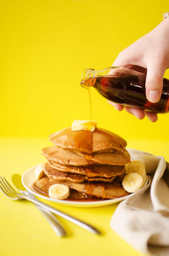 Pouring syrup over a stack of pancakes with yellow background