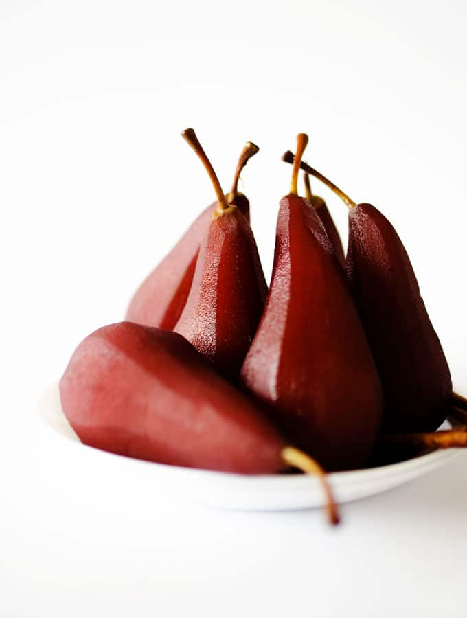 Red wine poached pears on a white background