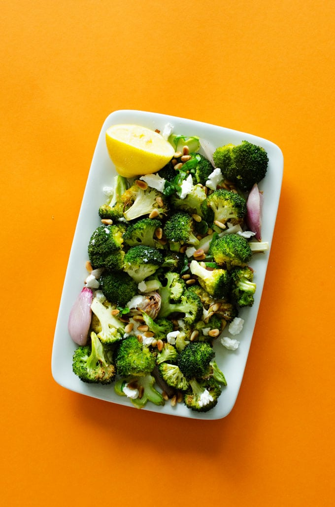 Roasted broccoli on a plate with orange background