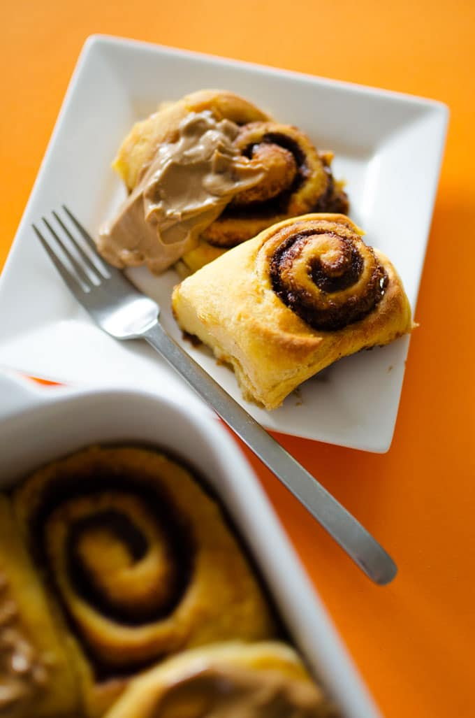 Sweet potato cinnamon rolls on a plate with frosting on an orange background.