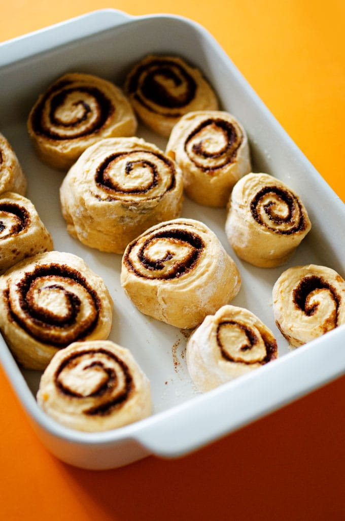 Cinnamon rolls in a pan with frosting on an orange background.