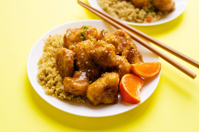 Cauliflower on a plate with yellow background - Think cauliflower is boring? Dress it up in a quick panko coating and sticky Asian-style sauce and I promise your mind will be changed! I give to you, Sticky Orange Cauliflower!