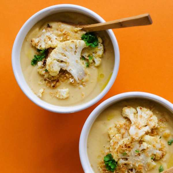 Cauliflower soup in a white bowl on orange background - Healthy Cauliflower Soup that's ultra-creamy AND easy AND vegan? It's happening and it is so much tastier that you can imagine.