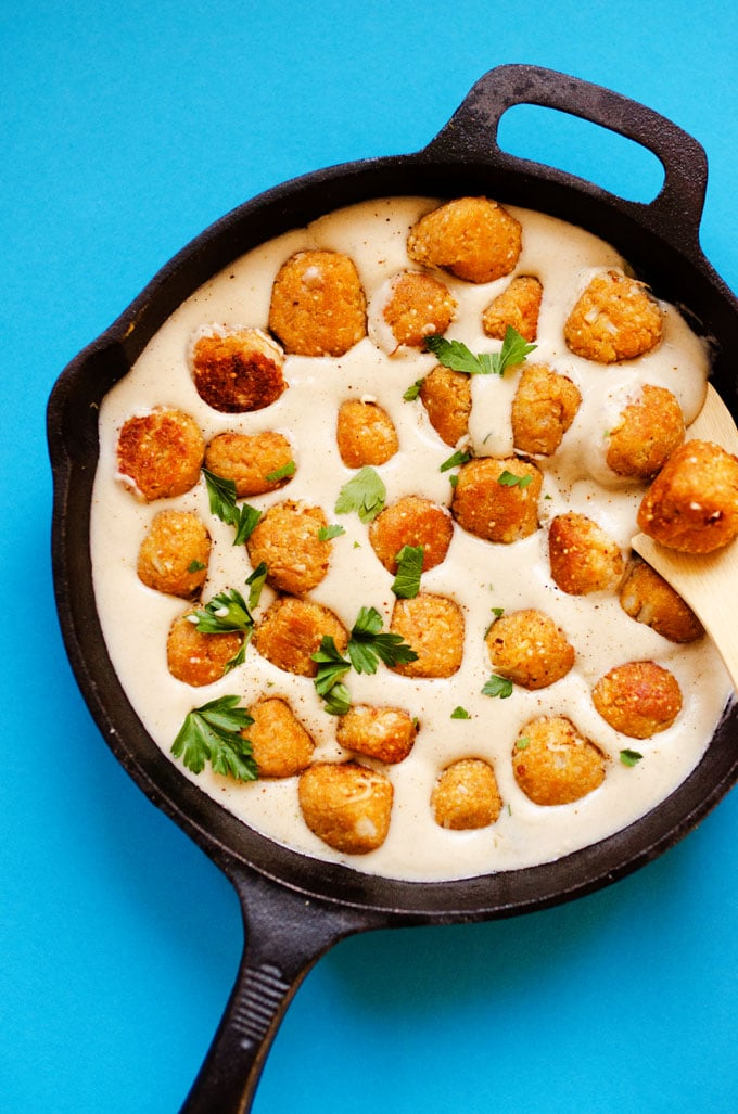 Photo of vegetarian Swedish meatballs in cream sauce in a cast iron skillet