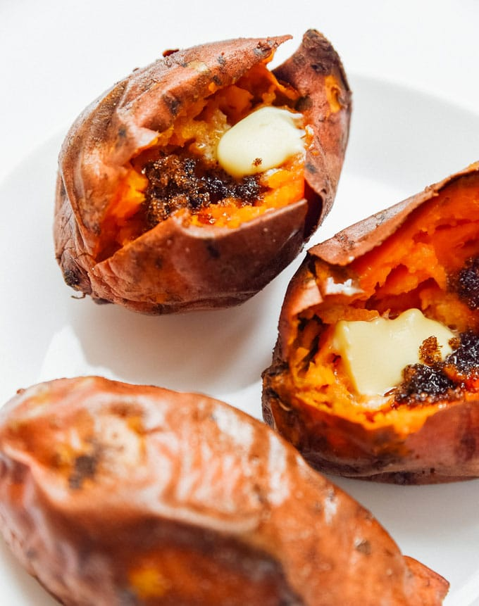 Air fryer sweet potatoes on a white background - The ultimate guide on how to cook air fryer potatoes! How to make roasted potatoes, homemade French fries, and potato chips in your air fryer, using both white potatoes and sweet potatoes.