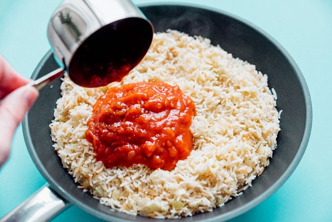 Adidng salsa to rice for Mexican Rice and Beans