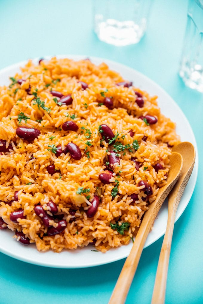 Spanish rice and red beans on a plate with a blue background - This easy vegan Spanish Rice and Beans recipe is quick to whip up and is a great source of complete proteins!