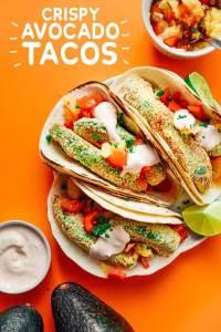 Vegetarian avocado tacos on an orange background - Creamy, crispy avocado tacos with fresh pineapple salsa and a quick yogurt sauce, perfect for your vegetarian Taco Tuesdays!
