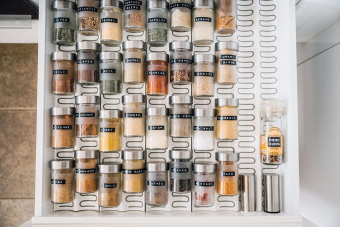 Organize spice drawer in minimalist white kitchen - How to clean out and organize your spice drawer like a pro! Spend less time looking for spices and more time cooking (and eating) tasty food).