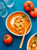 Fresh tomato soup in a bowl with homemade croutons and roma tomatoes