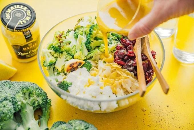 Pouring honey mustard dressing into broccoli salad