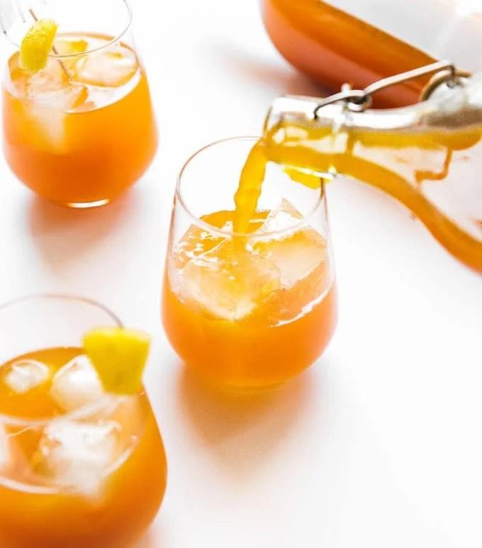 Pineapple basil kombucha in a glass on a white background