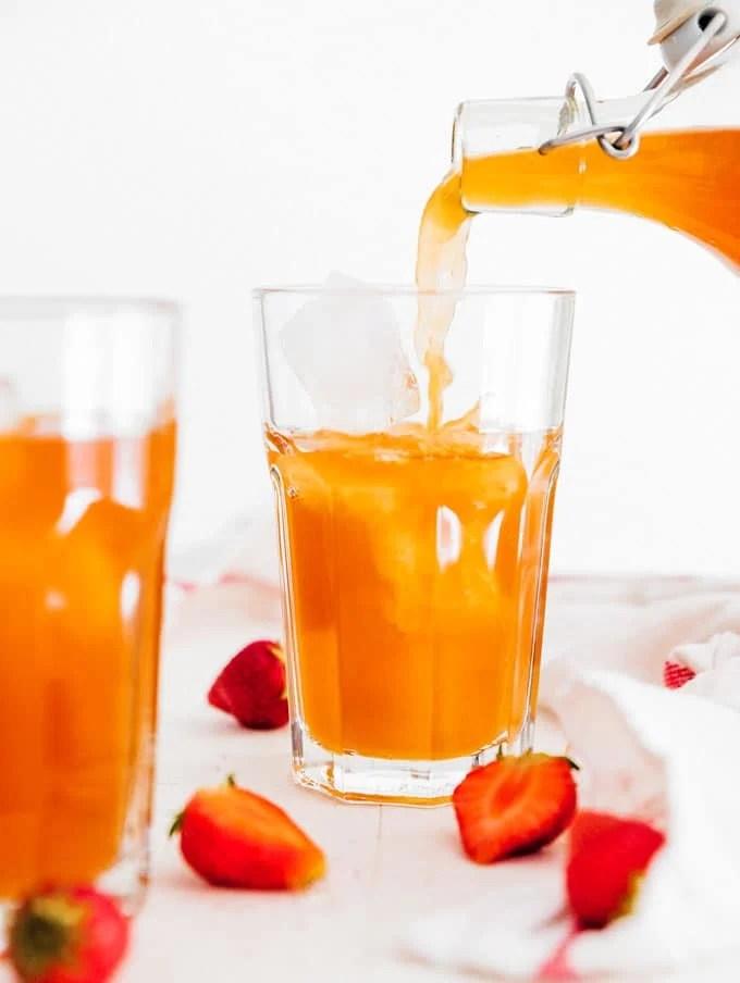 Pouring homemade strawberry kombucha into a glass