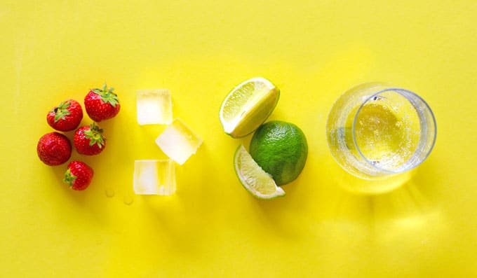 Ingredients to make strawberry limeade on a yellow background