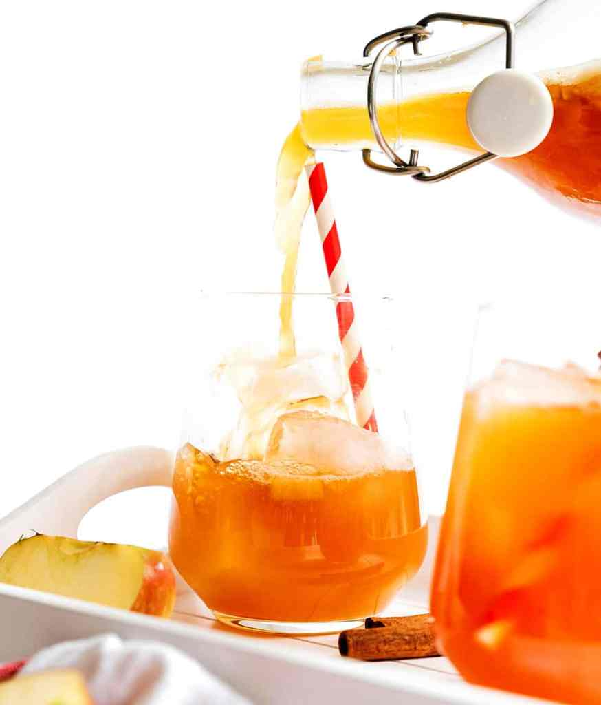 Pouring apple cinnamon kombucha into a glass with a white background