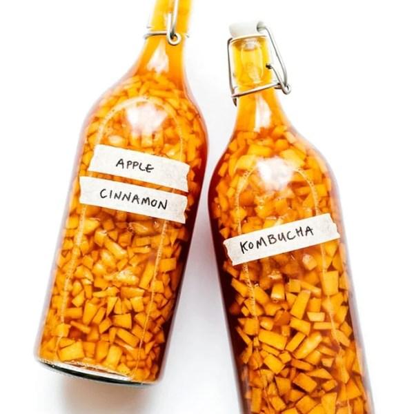 Apple kombucha in fermentation bottles on a white background