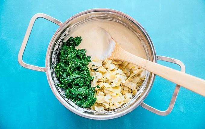 Ingredients to make greek yogurt spinach artichoke dip in a stove pan