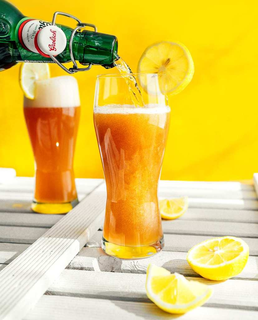 Pouring Grolsch beer into a glass with a yellow background