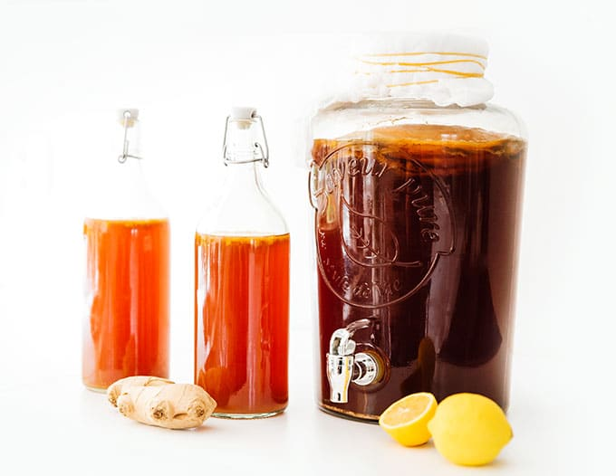 Ingredients to make lemon ginger kombucha on a white counter