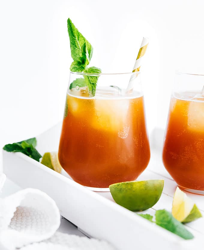 Mojito flavored kombucha in a glass with ice and a paper straw
