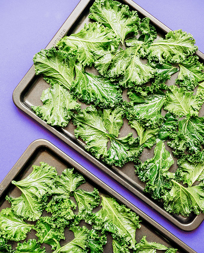 Baking sheet of kale chips on a purple background