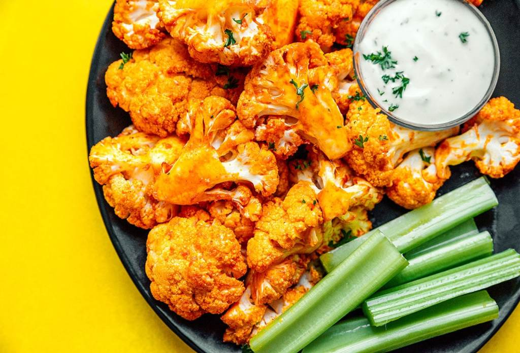 Buffalo cauliflower, celery, and dip on a black plate on a yellow background
