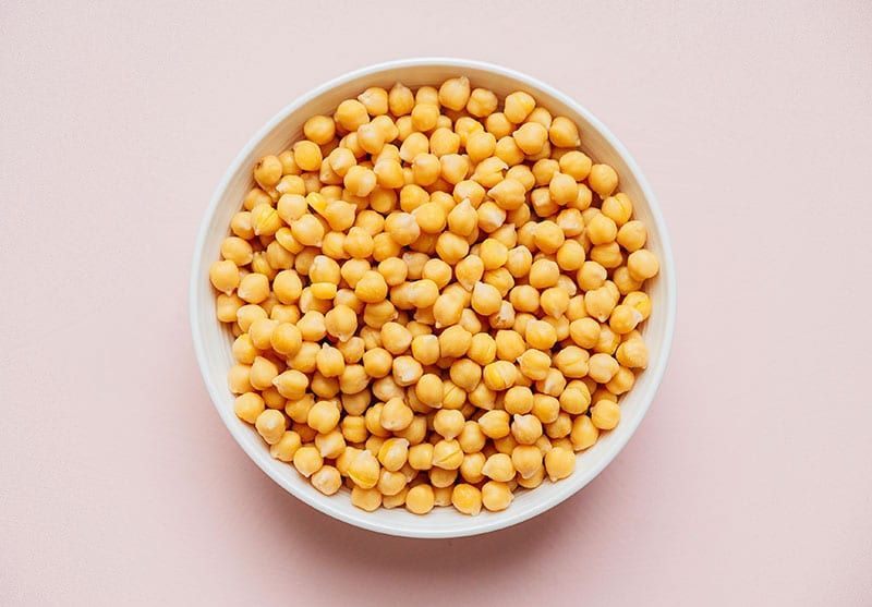Uncooked chickpeas in a bowl on a beige background