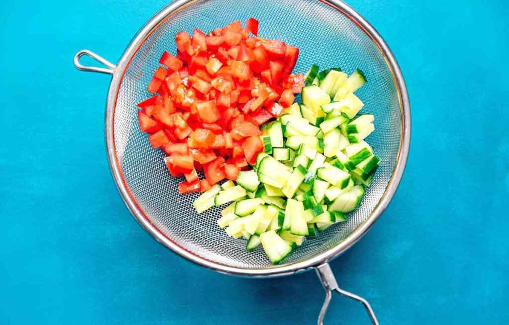 Chopped tomato and cucumber in a colander on a blue background