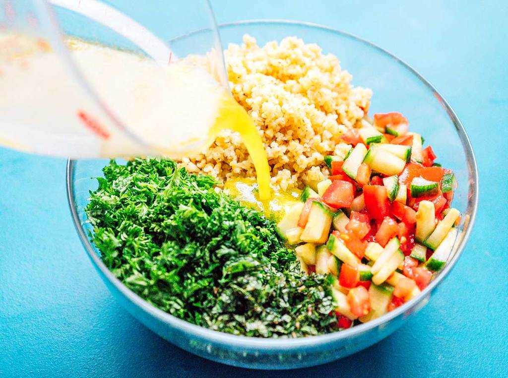 Pouring the dressing over a glass bowl filled with bulgur, tomato, cucumber, parsley, and mint