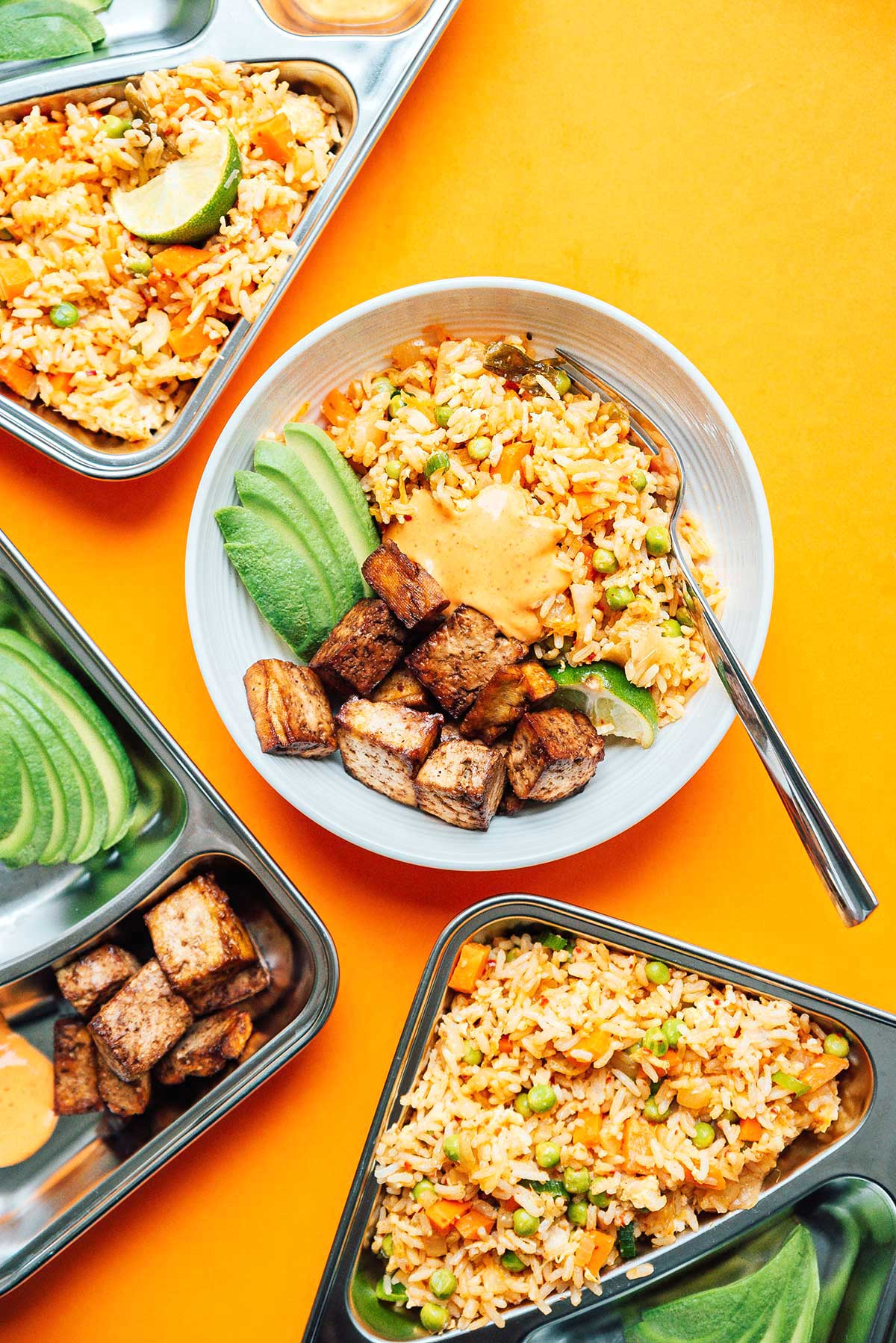 Kimchi fried rice meal prep in various bowls and containers on a yellow background