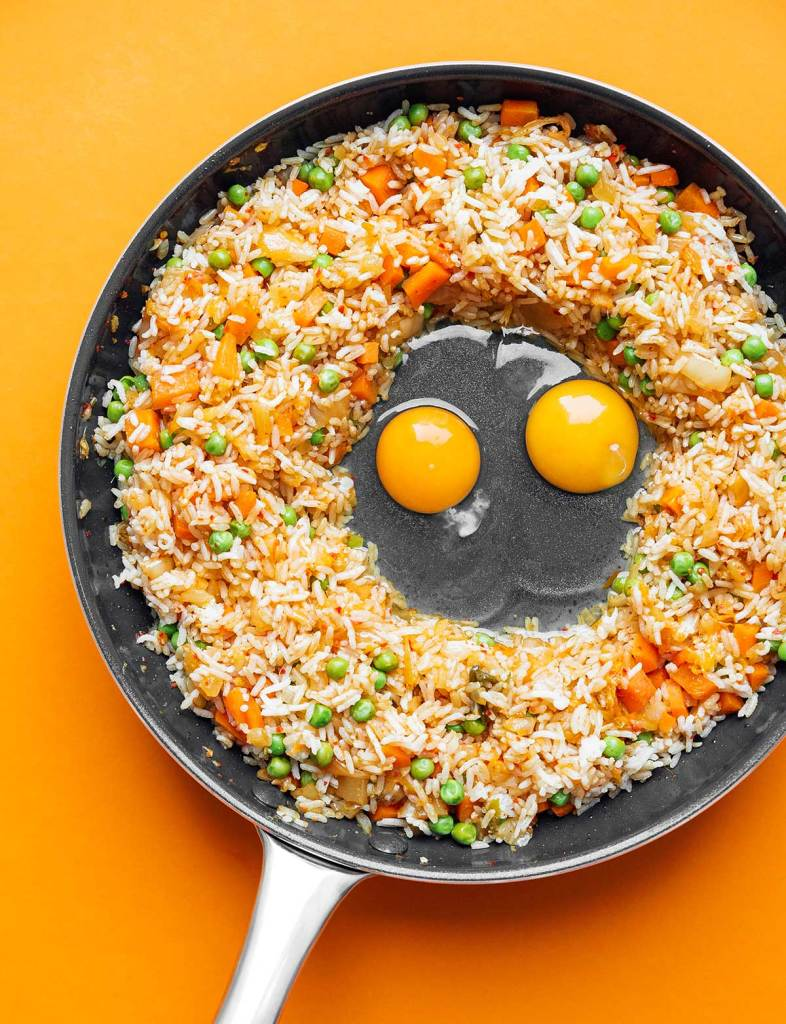Vegetables, kimchi, rice, and eggs cooking in a skillet on an orange background