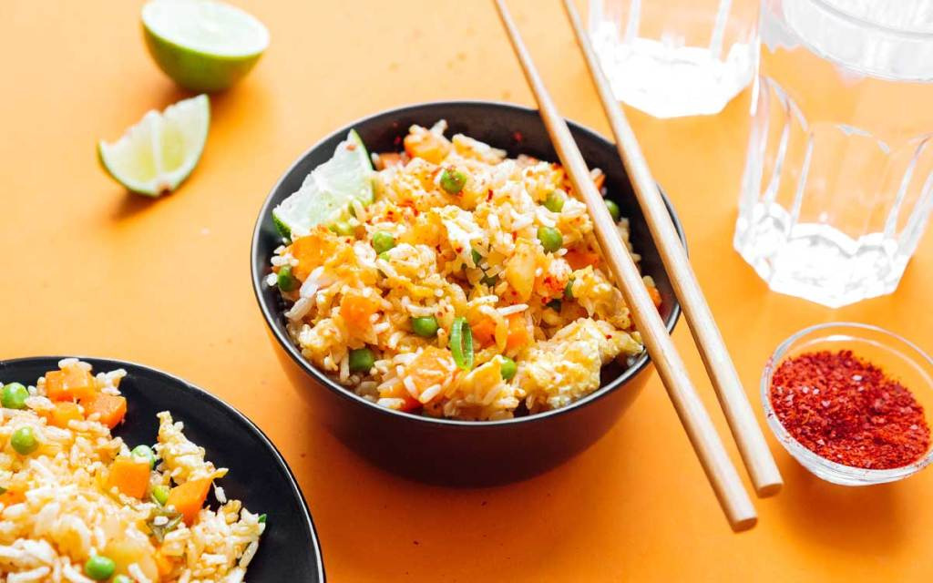 Two bowls of kimchi fried rice on an orange background