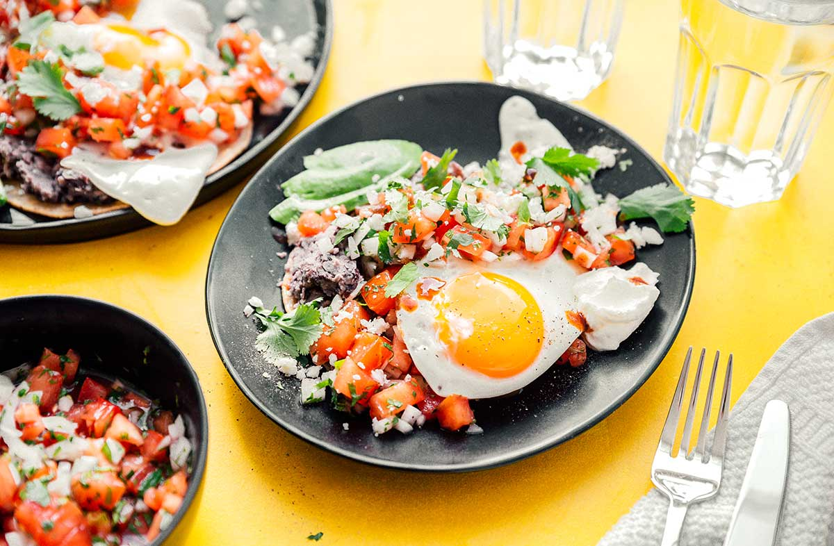 Two plates of huevos rancheros accompanied by water and pico de gallo