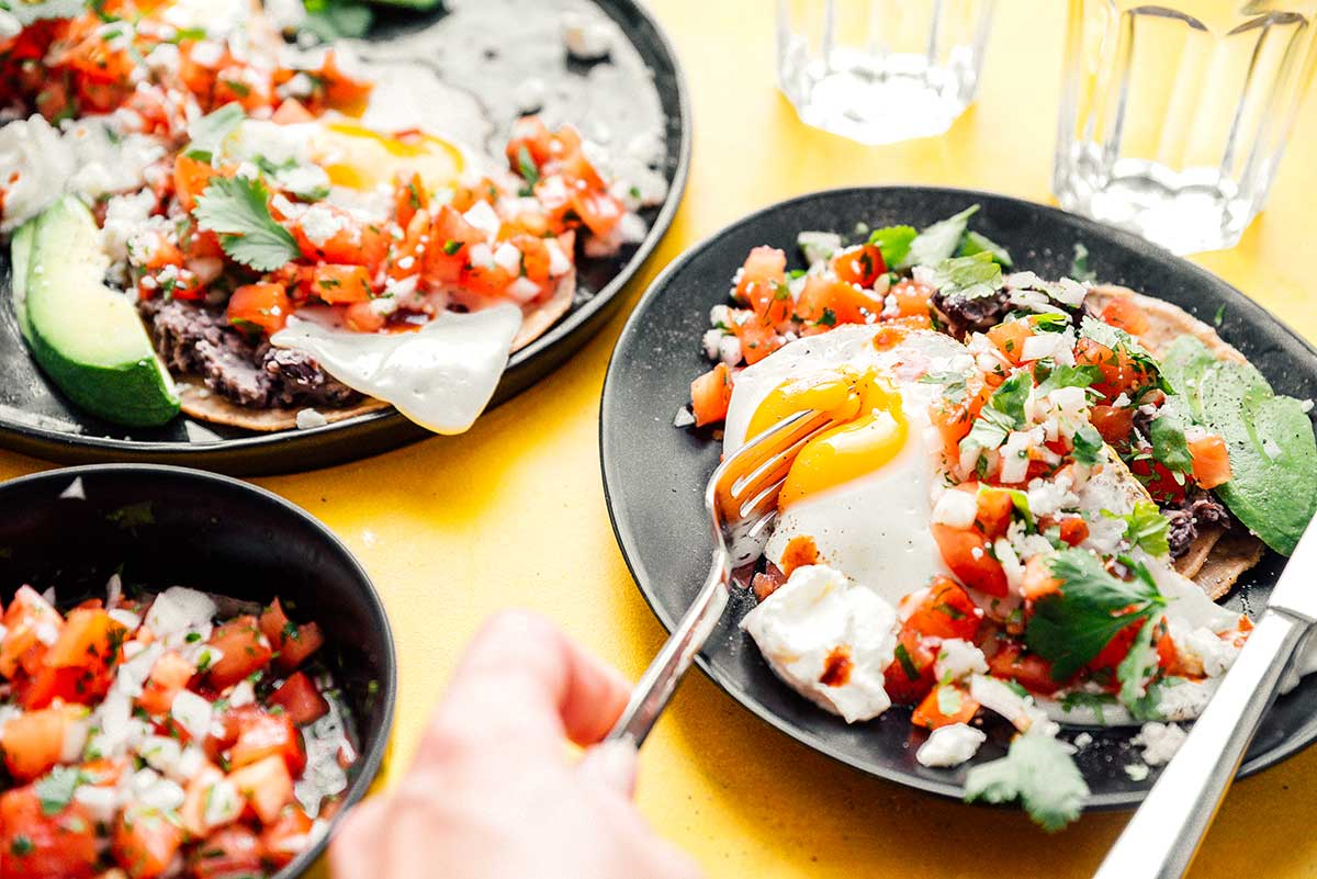 Two plates of huevos rancheros and a bowl of pico de gallo on a yellow background