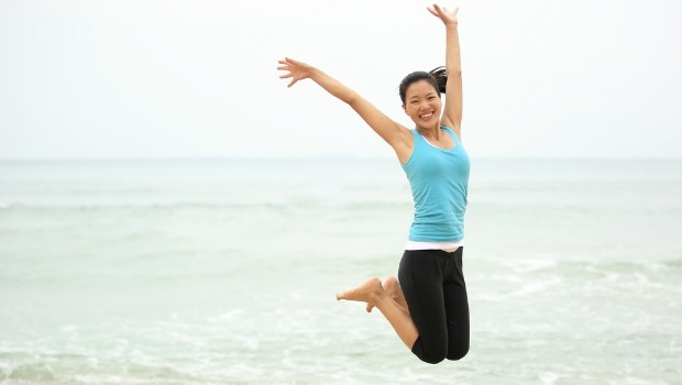 Healthy woman jumping on the beach