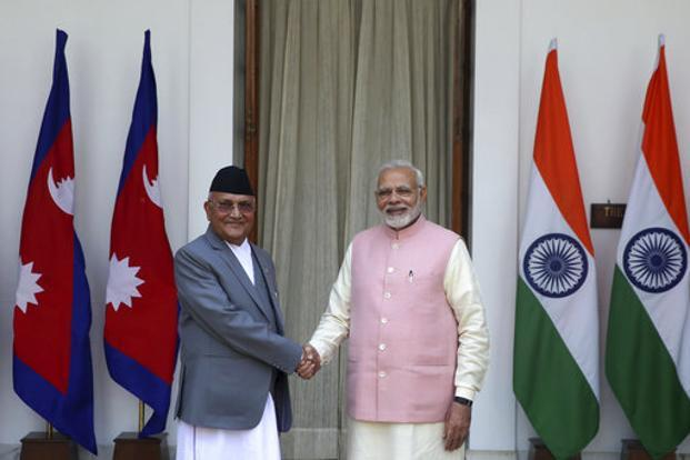 Prime Minister Narendra Modi with Nepalese Prime Minister K.P. Oli as they arrive for a bilateral meeting at Hyderabad house in New Delhi on Saturday. Photo: AP