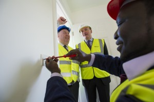 Mayor Joe Anderson and Sanctuary's chief operating officer Ian McDermott look on as City Of Liverpool College student Mani Mango carries out electrical work
