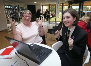 Beth Anderson, 15, shows Jean Handley how to access online services