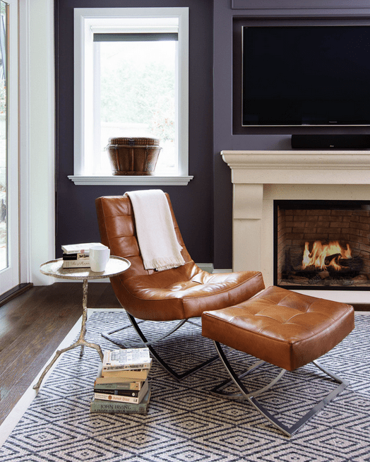 leather reading chair, dark walls and patterned rug make this space by Meghan Carter Design Inc. super inviting.