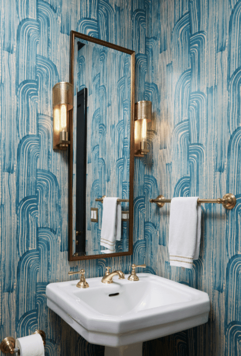 Brightly colored Kelly Wearstler Crescent Wallpaper covers the walls of this stunning powder room featuring a brass vanity mirror flanked by brass sconces mounted above a white pedestal sink finished with a polished brass vintage faucet kit complementing the brass towel bar fixed on an adjacent wall.