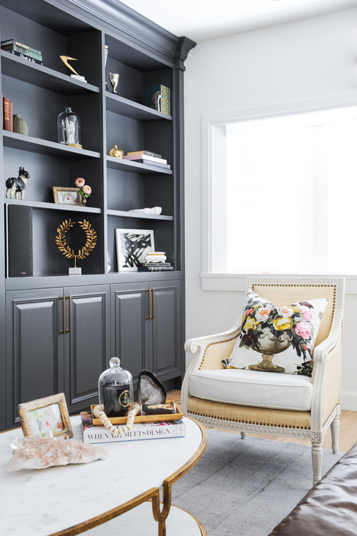 Beautifully styled built-in bookshelves and an elegant accent chair.