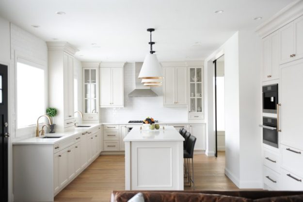 Beautiful white kitchen with large island, bar stools, and brass fixtures.