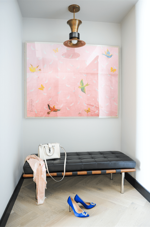 Perfectly sophisticated yet simple entryway with black, leather bench, whimsical pink artwork, and amazing (it must be vintage!) light fixture.