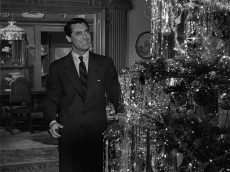 Cary Grant in front of the tinseled Christmas tree