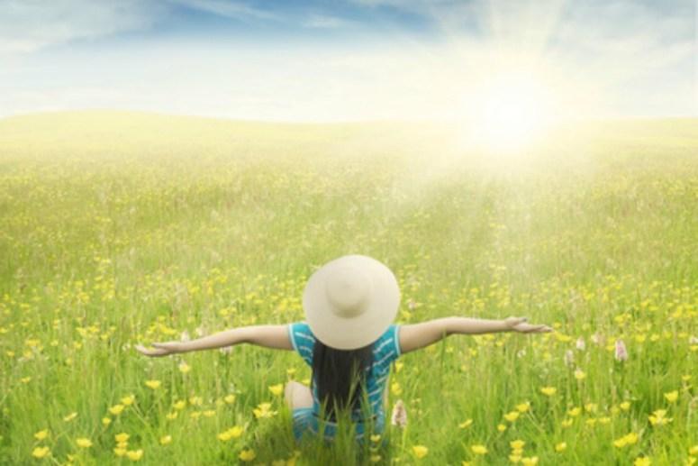 A woman breathing easy in a sun-lit field