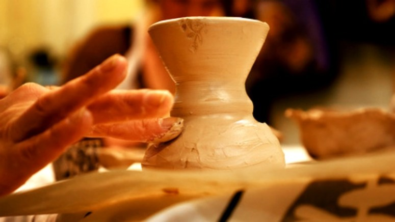 Someone using a spinner to create a clay pot