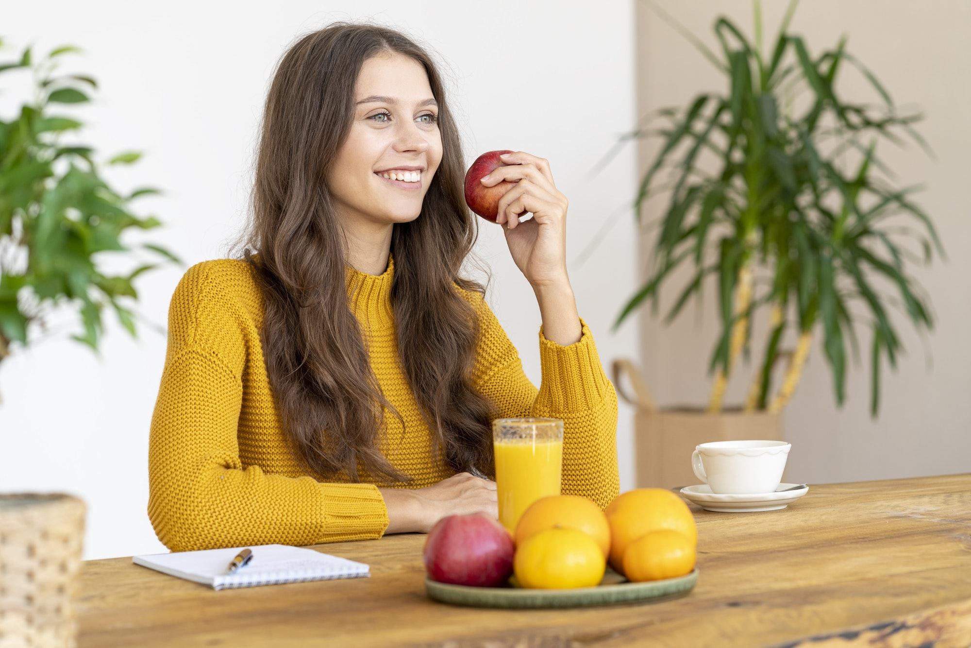 Young girl bitting red apple, smiling. Beautiful woman with long hair i